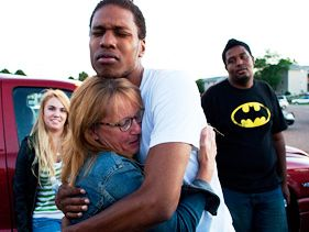 Judy Goos hugs her daughters friend, Isaiah Bow, 20 outside Gateway High School where witnesses were brought for questioning Friday, July 20, 2012 in Denver