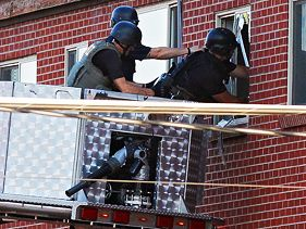 Police use a video camera to look inside the suspect's apartment in Colorado on Friday